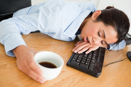 Attractive woman sleeping on a keyboard while holding a cup of coffee at the office photo