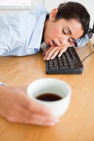 Gorgeous woman sleeping on a keyboard while holding a cup of coffee at the office photo