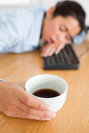 Cute woman sleeping on a keyboard while holding a cup of coffee at the office photo