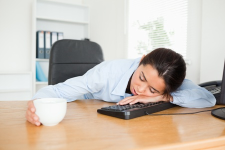 Frontal view of a pretty woman sleeping on a keyboard while holding a cup of coffee at the office photo
