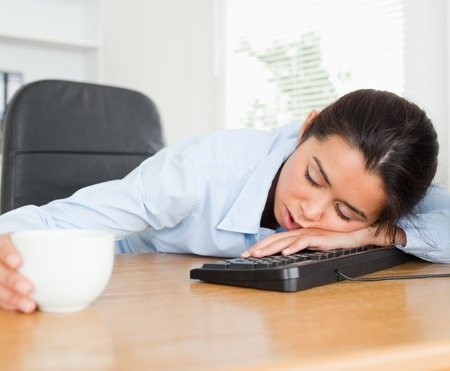 Frontal view of a beautiful woman sleeping on a keyboard while holding a cup of coffee at the office photo