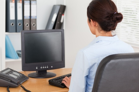 View from behind of a beautiful woman typing on a keyboard while working at the office photo
