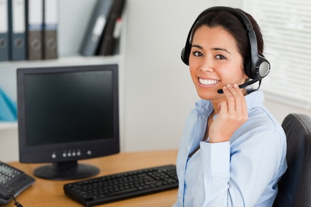 Beautiful woman wearing a headset and discussing while sitting at the office photo