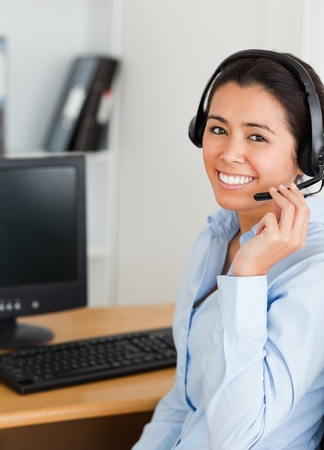 Attractive woman wearing a headset and discussing while sitting at the office photo