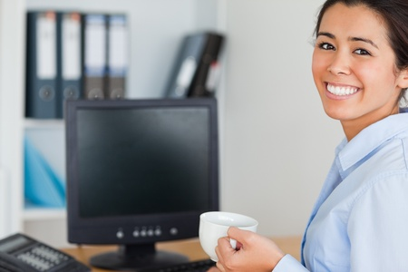 Good looking woman holding a cup of coffee while sitting at the office photo