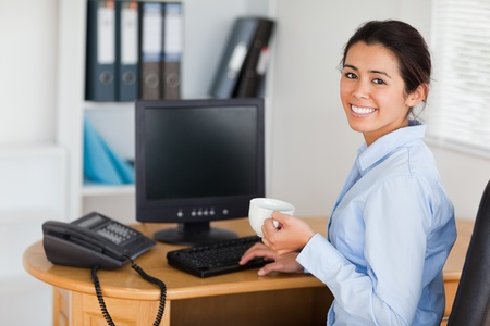 Attractive woman holding a cup of coffee while sitting at the office photo