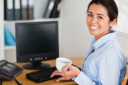 Beautiful woman holding a cup of coffee while sitting at the office photo