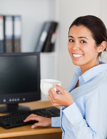 Pretty woman holding a cup of coffee while sitting at the office photo