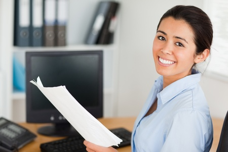 Attractive woman holding a sheet of paper and posing while sitting at the office photo