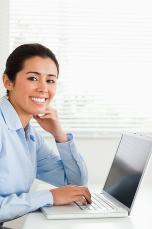 Charming woman working with her laptop and posing while sitting at the office photo