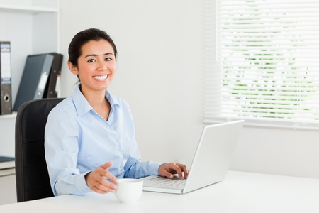 Beautiful woman relaxing with her laptop while enjoying a cup of coffee at the office photo
