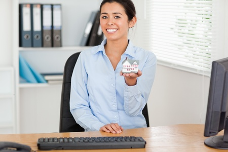 Beautiful woman holding a miniature house while looking at the camera at the office photo