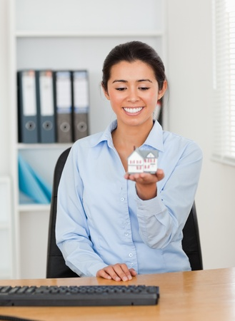 Attractive woman holding a miniature house while looking at the camera at the office photo