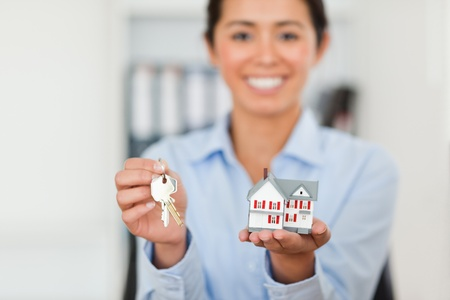 Attractive woman holding keys and a miniature house while looking at the camera at the office photo