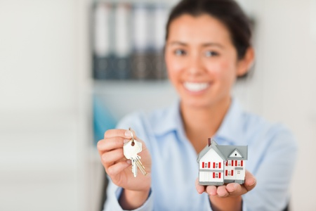 Good looking woman holding keys and a miniature house while looking at the camera at the office photo