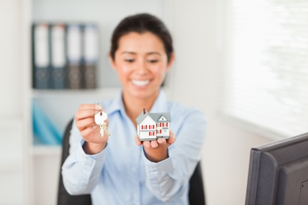 Pretty woman holding keys and a miniature house while looking at the camera at the office photo