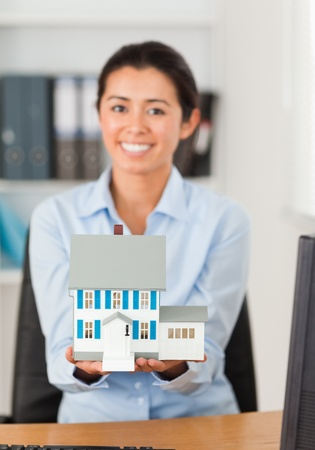 Gorgeous woman holding a miniature house while looking at the camera at the office photo