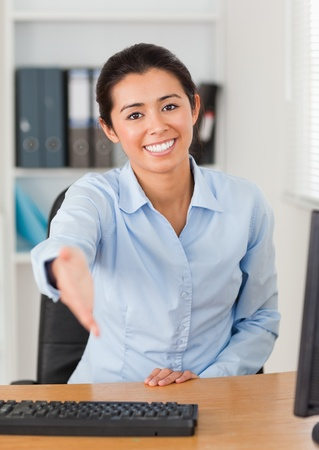 Beautiful woman inviting somebody to seat while looking at the camera at the office photo