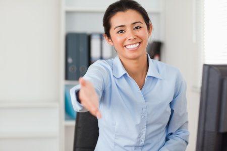 Good looking woman inviting somebody to seat while looking at the camera at the office photo