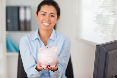 Attractive woman holding a piggy bank while looking at the camera at the office photo