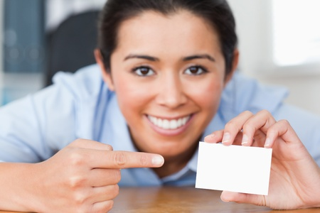 Attractive woman showing her visiting card at the office photo