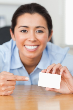 Charming woman showing her visiting card at the office photo