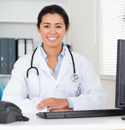 Beautiful woman doctor with a stethoscope posing in her office photo