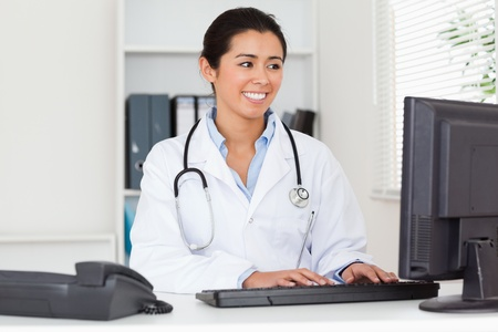 Attractive woman doctor typing on a keyboard in her office photo