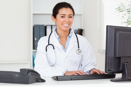 Good looking woman doctor typing on a keyboard in her office photo