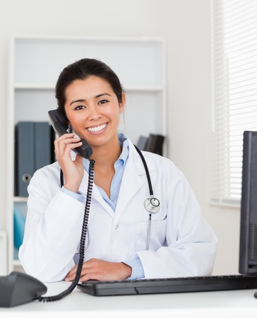 Good looking woman doctor on the phone while sitting in her office photo
