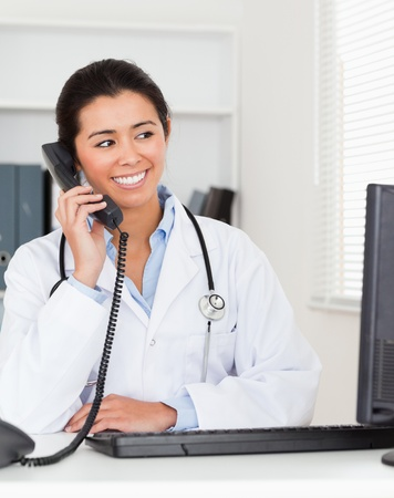 Beautiful woman doctor on the phone while sitting in her office photo