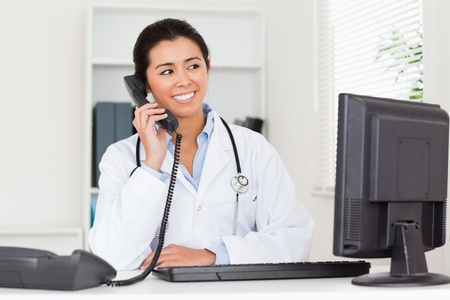 Attractive woman doctor on the phone while sitting in her office photo