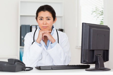 Lovely worried woman doctor looking at the camera while sitting in her office photo