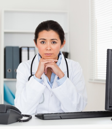 Beautiful worried woman doctor looking at the camera while sitting in her office photo