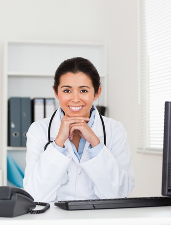 Beautiful woman doctor posing while sitting in her office photo
