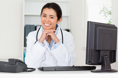 Attractive woman doctor posing while sitting in her office photo