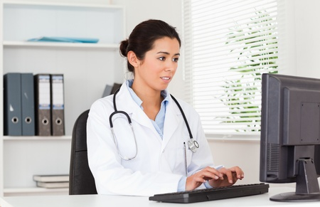 georgeous: Georgeous female doctor typing on a keyboard while sitting in her office Stock Photo