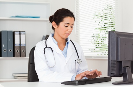 Charming female doctor typing on a keyboard while sitting in her office photo