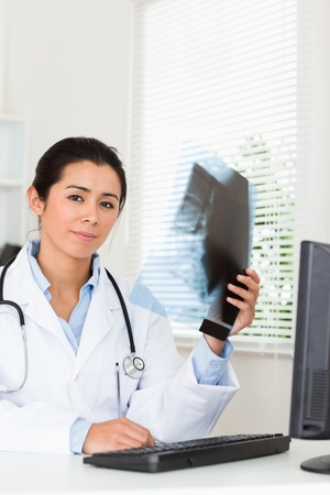 Good looking female doctor looking at a x-ray in her office photo