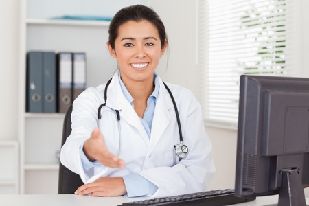 Pretty female doctor inviting somebody to seat while looking at the camera in her office photo