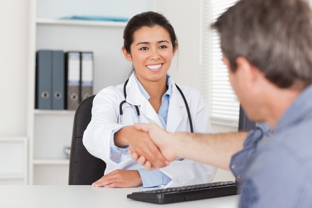 Pretty female doctor shaking a patients hands in her office photo