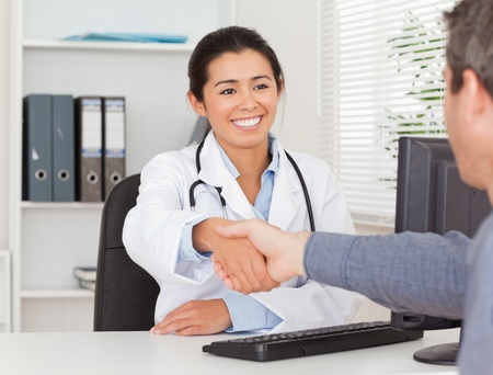 Beautiful female doctor shaking a patient's hands in her office photo