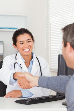 Attractive female doctor shaking a patients hands in her office photo