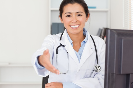 Attractive female doctor inviting somebody to seat while looking at the camera in her office photo