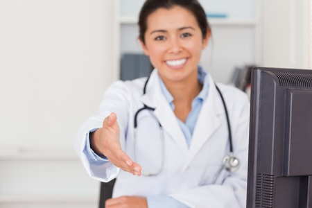 Beautiful female doctor inviting somebody to seat while looking at the camera in her office photo