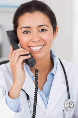 Pretty female doctor on the phone and posing in her office photo