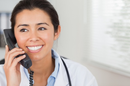 Attractive female doctor on the phone and posing in her office photo