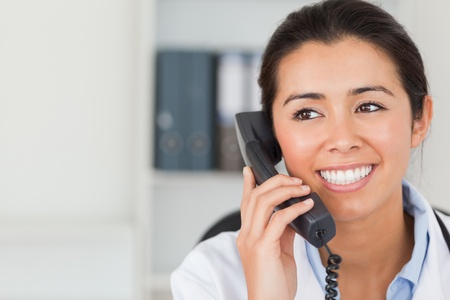 nurse computer: Good looking female doctor on the phone and posing in her office Stock Photo