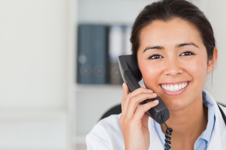 Gorgeous female doctor on the phone and posing in her office photo