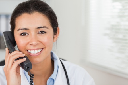 phoning: Lovely female doctor on the phone and posing in her office